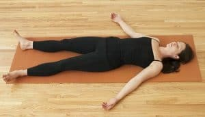 Young woman lying on yoga mat --- Image by Helen King/Corbis